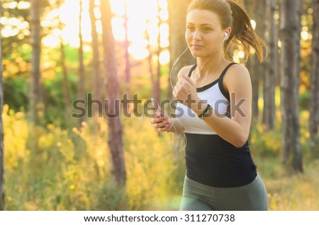Runner athlete running on forest trail. woman fitness jogging workout wellness. Soft Focus