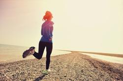 Runner athlete running on stone beach. woman fitness jogging workout wellness concept.