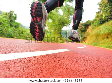 Runner athlete running on trail. woman fitness jogging workout wellness concept.