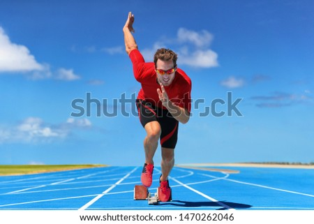 Runner athlete starting running at start of run track on blue running tracks at outdoor athletics and fiel stadium. Sprinter on race. Sport and fitness man sprinting.