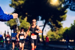 Runner collects a bottle of water to hydrate during a workout.