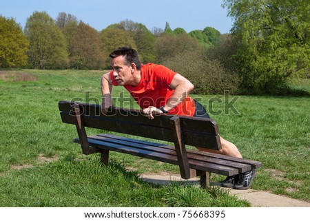 Runner doing pressups on a Park Bench
