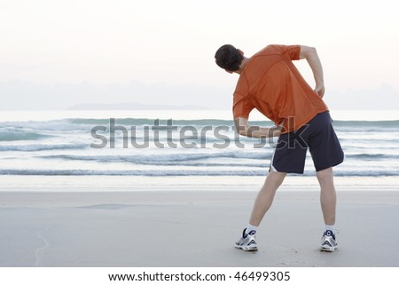 Runner doing stretching exercises on a beach early in the morning
