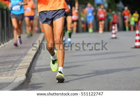 runner during race walking in the city with many athletes from all nations #551122747