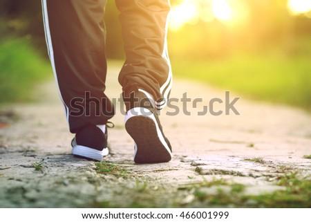 Runner feet running on concrete road in park - fitness sunrise jog workout welness concept Stock fotó ©