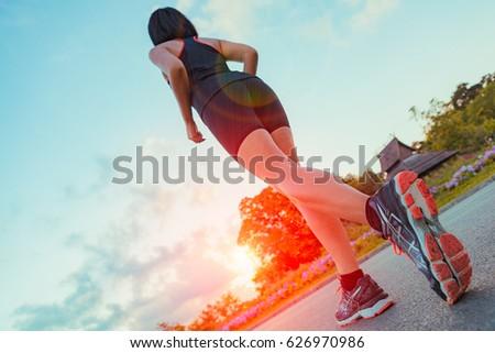 runner feet running on road at...