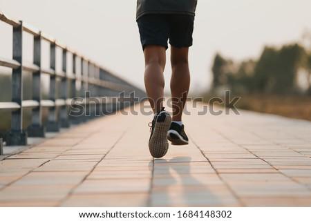 Runner feet running on road closeup on shoe. MAN fitness sunrise jog workout welness concept.