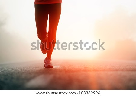 Runner feet running on road closeup on shoe. woman fitness sunrise jog workout welness concept. - stock photo