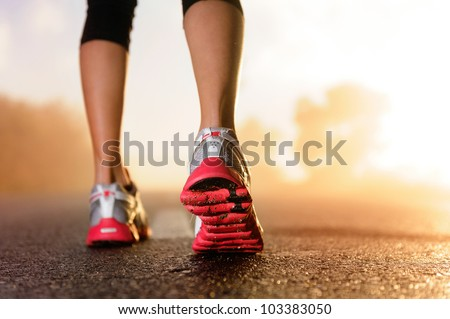Runner feet running on road closeup on shoe. woman fitness sunrise jog workout welness concept.