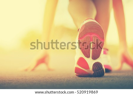 Runner feet running on road closeup on shoe. woman fitness sunrise jog workout welness concept on sunset. Vintage tone.