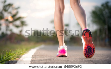 Runner feet running on running road closeup on shoe. woman fitne #545593693