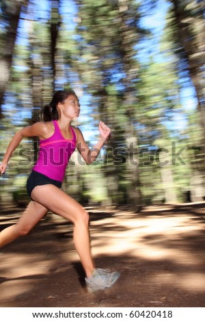 Runner, Female running fast in forest. Motion blurred image of beautiful Asian / Caucasian woman athlete sprinting outdoors in tank top - copy space.