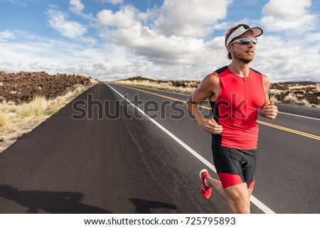 Runner fit athlete man running in triathlon suit training for Iron man on Hawaii. Fit male triathlete exercising endurance cardio on road. #725795893