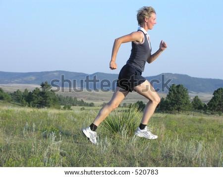 Runner in field at sunset