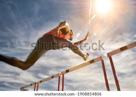 Runner jumping over running hurdle, low angle view Сток-фото ©