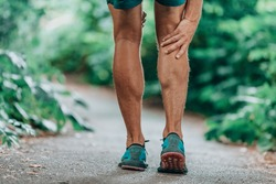 Runner leg injury painful leg. Man massaging sore calf muscles during running training outdoor from pain.
