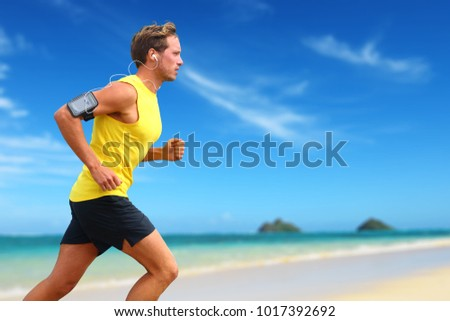 Runner listening smartphone music running on beach. Lanikai, Oahu, Hawaii, USA. Male athlete jogging on ocean beach or waterfront working out with smart phone app device and earphones in summer. #1017392692