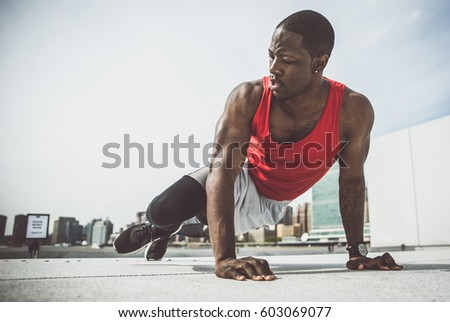 Runner making some exercises on the fence