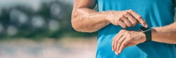 Runner man athlete checking heart rate monitor during workout on wearable tech smartwatch banner panorama.