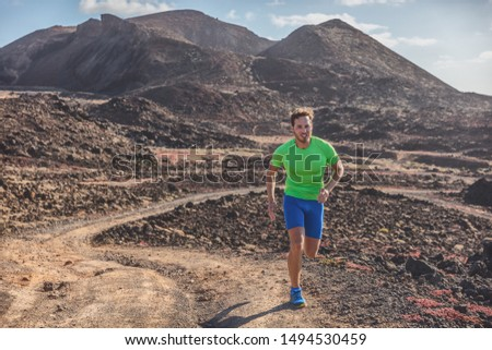 Runner man athlete running on trail run outdoor mountains landscape. Difficult endurance training ultra running marathon race in sun.
