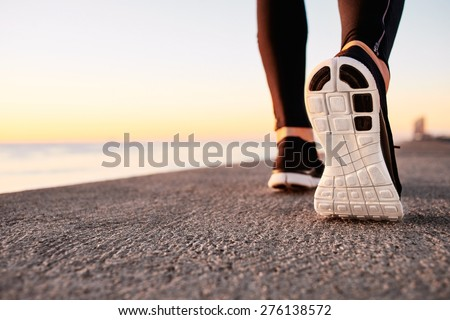 Runner man feet running on road closeup on shoe. Male fitness athlete jogger workout in wellness concept at sunrise. Sports healthy lifestyle concept.