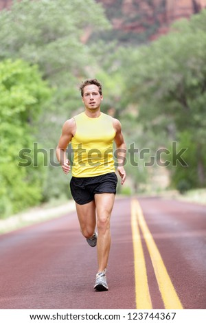 Runner man running with concentration, determination and strength in full length on road. Fit male sport fitness model sprinting outdoors.