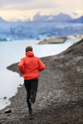 Runner man trail running training for run in beautiful nature landscape. Fit male athlete jogging and cross country running by icebergs in Jokulsarlon glacial lake in Iceland.