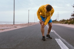 Runner man with knee injury and pain on the road