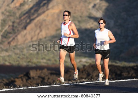 Runner men running marathon training run on road in amazing mountain landscape. Two men jogging in sporty outfit.