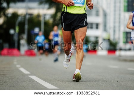 runner middle-aged man running down street marathon city #1038852961