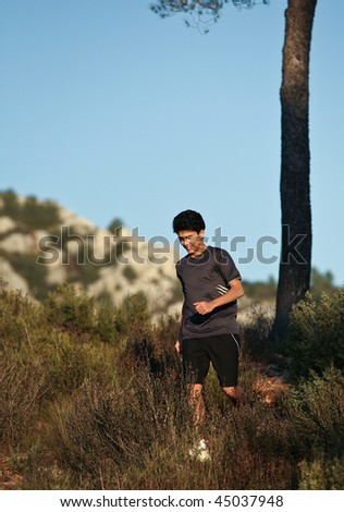 Runner moving through sunlit landscape