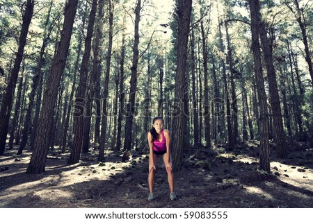 Runner relaxing after running in atmospheric enchanted forest. Beautiful woman model.