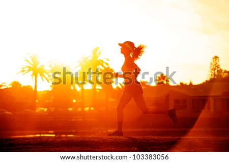 Runner running in a suburb, healthy fitness wellness vitality athlete silhouetted against the sun flare - stock photo