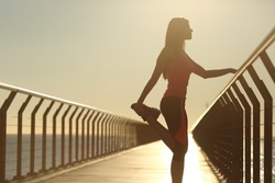 Runner silhouette doing stretching exercises at sunset in a bridge on the beach