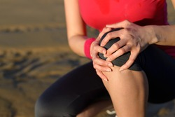 Runner sport knee injury. Woman in pain while running in beach.