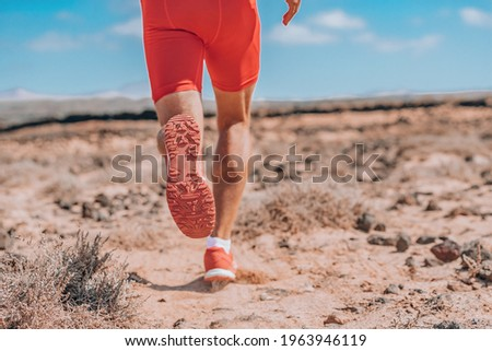 Runner sprinting running away rear view closeup of red shoes. Training triathlon athlete on trail run outdoor exercise endurance workout. ストックフォト ©