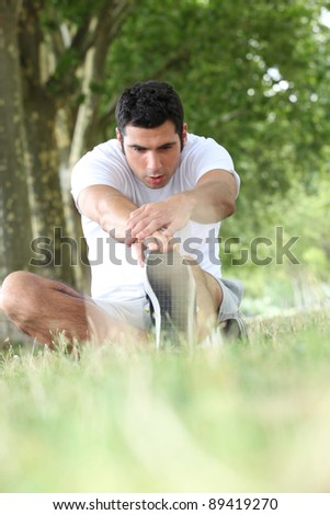 Runner stretching on grass