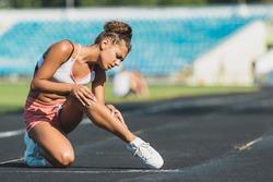 Runner suffering from leg cramp on the track