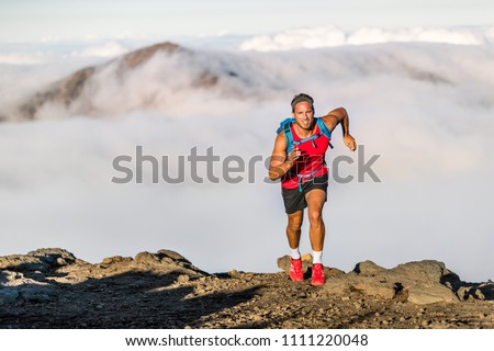 Runner trail running fitness man on endurance run - motivation and concentration on race in sky and clouds background on nature landscape. Focused athlete with backpack and hairband training cardio.