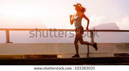 runner training at sunset, silhouette of fitness marathon woman with lens flare and action