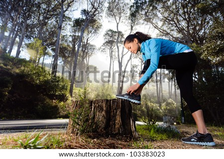runner tying her shoelace while preparing for fitness training outdoors in the forest with morning sunlight
