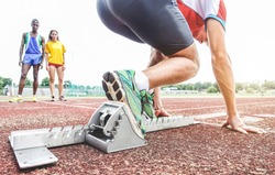 Runner using starting block to start his run on race track - Young athlete starting his sprint on running track -  Healthy lifestyle, sport, comtetiotn and goal concept - Focus on right shoe