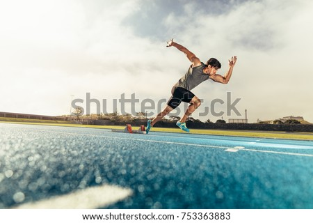 Runner using starting block to start his run on running track. Athlete starting his sprint on an all-weather running track with the help of starting block. #753363883