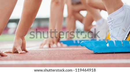 Runner waiting behind the start line ready to run at starting blocks