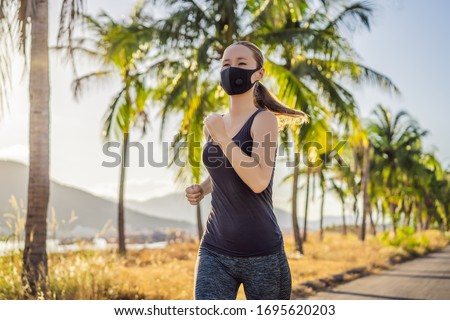 Runner wearing medical mask, Coronavirus pandemic Covid-19. Sport, Active life in quarantine surgical sterilizing face mask protection. Outdoor run on athletics track in Corona Outbreak. Keep your