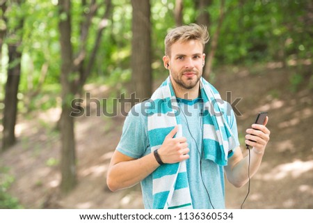runner with mp3. man runner listen music on mp3 player. mp3 in hand of man runner. runner sportsman with mp3 player