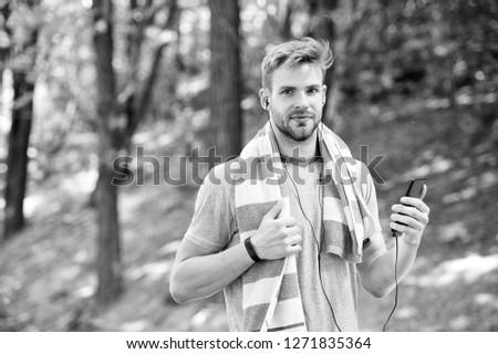 runner with mp3. man runner listen music on mp3 player. mp3 in hand of man runner. runner sportsman with mp3 player