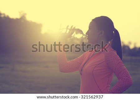 Runner woman drinking water #321562937