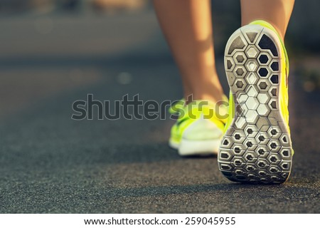 Shutterstock Runner woman feet running on road closeup on shoe. Female fitness model sunrise jog workout. Sports healthy lifestyle concept.