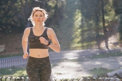Runner woman getting ready to run and starts running in wearing earphones listening to music